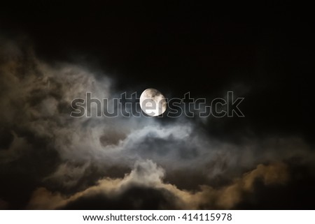 full moon surrounded by dark clouds at night
