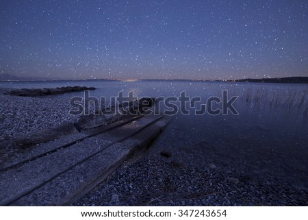 full moon, which is mirrored in the lake while it snows - stock photo