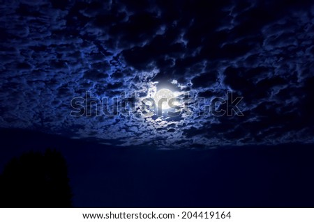 Full moon with indigo hues glowing in night sky illuminating clouds in wide angle perspective/Full moon glowing in night sky illuminating cloud cover - stock photo