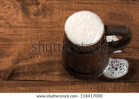 Full mug of fresh beer on a wooden table. View from above. - stock photo