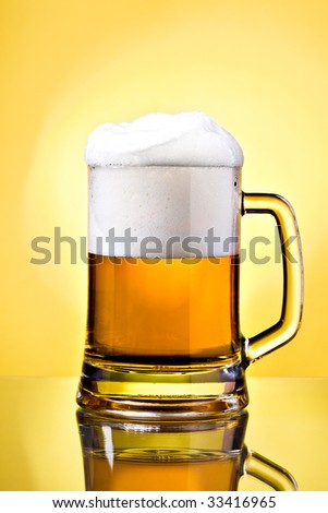 Full mug of lager beer on yellow - stock photo