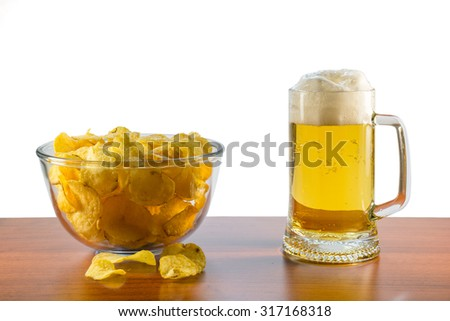 Full mug of lager beer with foam and glass bowl of potato chips stand on the table on a white background - stock photo