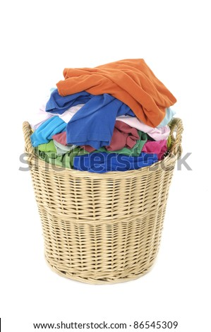 full of colorful shirts in a wicker basket, isolated