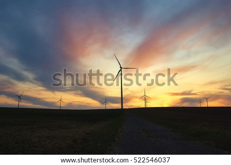 Full of colors dramatic sunset with windmill at power plant area in Austria