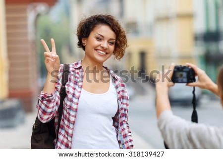 Full of energy. Overjoyed nice young girl holding her hand up and expressing positivity while posing in front of the camera