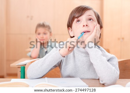 Full of ideas. Full of thoughts little boy during classes sitting at desk and looking upwards  with pen in his mouth. - stock photo