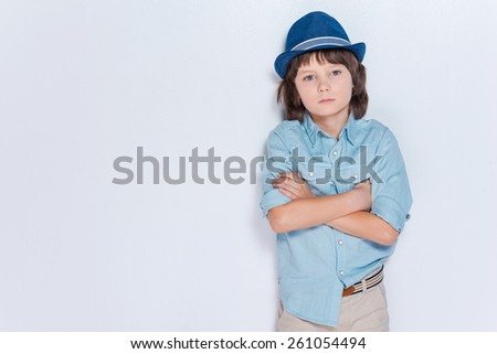 Full of inspiration.  Little boy wearing hat and keeping arms crossed while standing against white background - stock photo