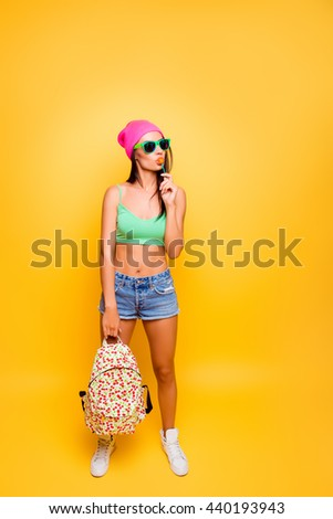 full photo of attractive funny young woman with backpack licking lollipop