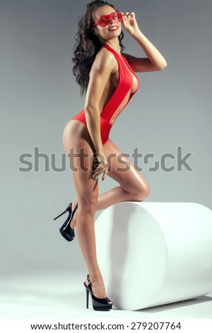 Full photo of sexy brunette woman with slim perfect body. Girl posing in red lingerie, smiling. Studio shot. - stock photo