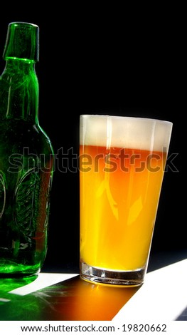 full pint of beer and bottle, on dark background