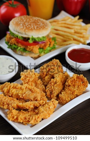 Full plate of crispy chicken sticks , burger and french fries. - stock photo