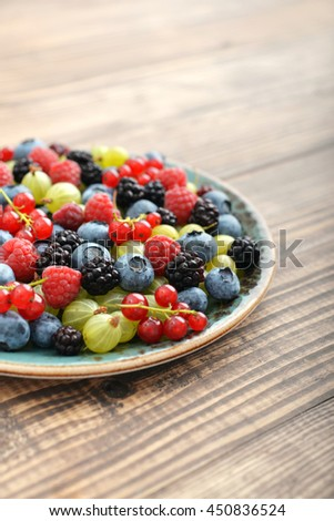 Full plate of juicy ripe summer berries on wooden background