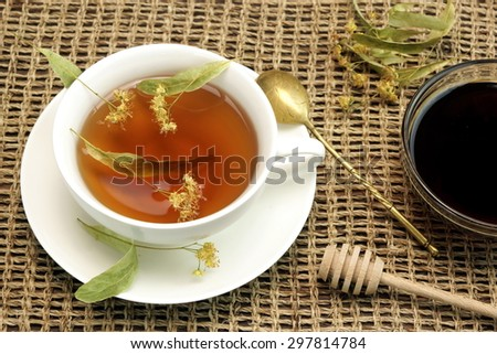 Full Porcelain Tea Cup With Herbal Lime Tree Blossom Green Tea, Glass Plate With Lime Tree Honey, Wood  Dipper And Old Gold Spoon On The Wicker Cloth - stock photo