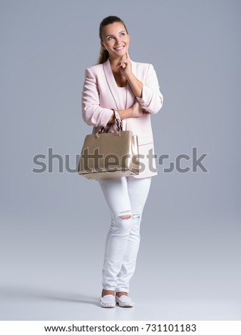 Full portrait of an young happy woman with handbag posing at studio