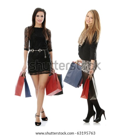 Full portrait of elegant two young women with shopping bags, isolated on white background - stock photo