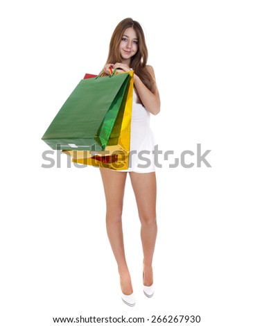Full portrait of smiling young blonde girl with colorful shopping bags in white dress posing on a white background - stock photo