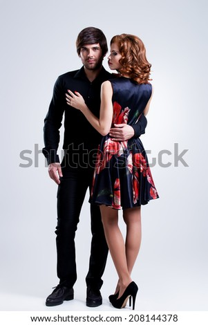 Full portrait of young couple in love posing at studio dressed in elegant clothes. - stock photo
