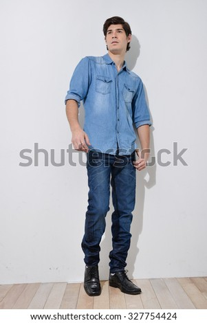 Full portrait of young man in jeans on wooden background - stock photo