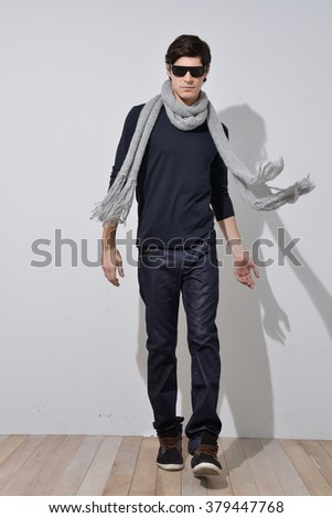 Full portrait of young man with scarf in full length over wooden background  - stock photo