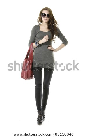 Full portrait of Young woman in sunglasses with handbag. walking - stock photo