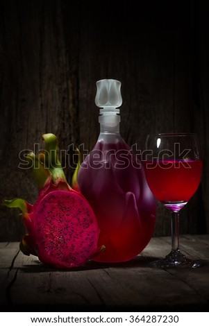 Full red Dragon Fruit wine glass goblet and bottle on wooden background - stock photo