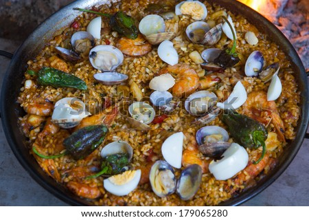 Full red pepper paella cooked on a wood fire at home with shrimp clams and green Padron peppers - stock photo