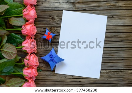 Full row of pink stemmed roses, diamond shaped gift boxes with little bows, blank white paper and purple ribbon on wood surface - stock photo