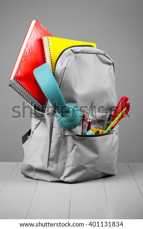 Full school backpack on grey background - stock photo