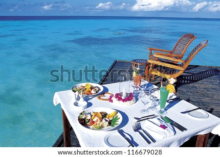 Full set of brunch on a table at the beach - stock photo