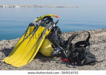 Full set of scuba diving equipment on the ground next to a tropical sea coast - stock photo