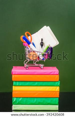 Full shopping cart standing on books near empty green chalkboard - stock photo