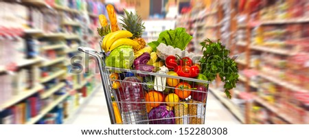 Full shopping grocery cart in supermarket. - stock photo