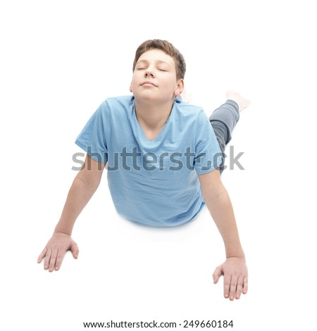 Full shot of a caucasian 12 years old childen boy in a blue t-shirt doing yoga or stretches. Composition isolated over the white background - stock photo