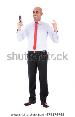 Full shot of a mature bald man smiling and looking to cellphone, guy wearing white shirt and red tie, isolated on white background