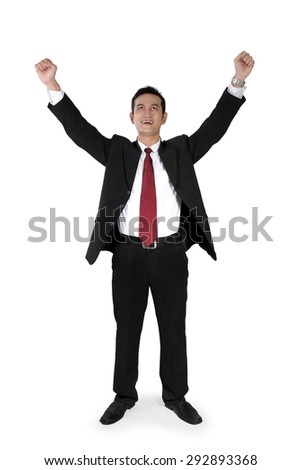 Full shot of attractive Asian businessman expressing happiness with both arms raised, standing perpendicular from the camera, isolated on white - stock photo