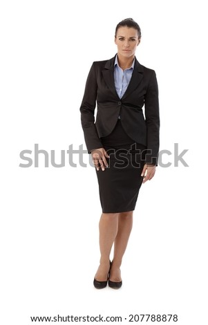 Full size portrait of serious casual brunette caucasian businesswoman wearing suit, standing in front of white background. Looking at camera. - stock photo