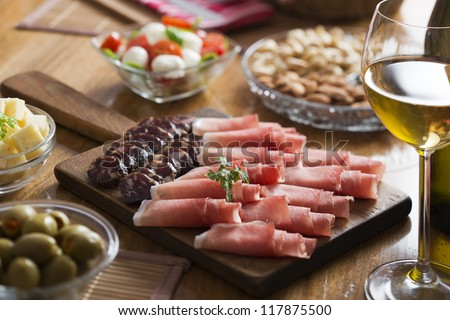 Full table of prosciutto, olives, cheese, salad and wine - stock photo