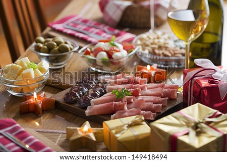 Full table of prosciutto, olives, cheese, salad and wine for holidays - stock photo