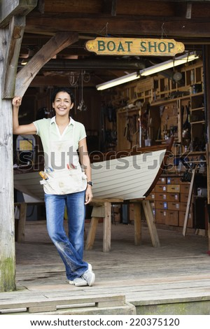 Full view portrait of woman standing at entrance to boat shop - stock photo