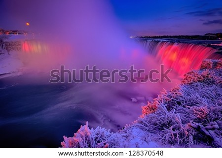 Full Wolf Moonrise over Illuminated Horseshoe Falls Surrounded with Ice, Snow, and Frost in Winter - stock photo