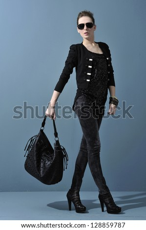 Full young woman in sunglasses with handbag. walking