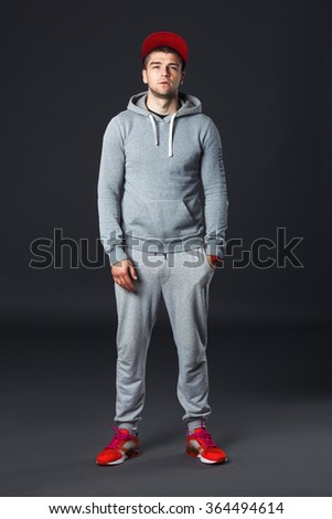 Fullbody portrait of young cool man standing  on dark gray background. - stock photo