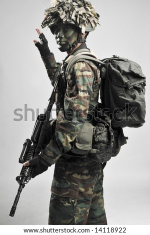 fully armed and equipped soldier giving hand signals