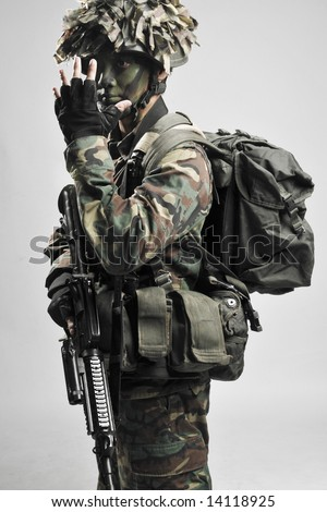 fully armed and equipped soldier giving hand signals - stock photo