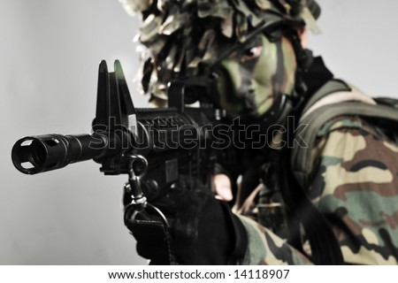 fully armed and equipped soldier taking aim