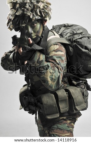 fully armed and equipped soldier taking aim - stock photo