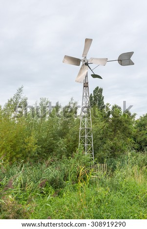 Fully automatic metal wind watermill in a nature reserve pumps the water out of a ditch not visible on the photo and rotates itself in the right wind direction.