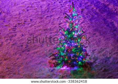 Fully decorated illuminated Christmas tree with ornaments on snowy spruce branches at Christmas night - stock photo