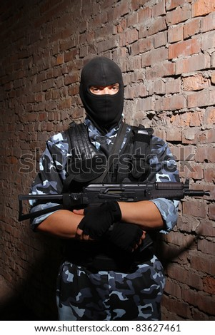 Fully equipped military men with automatic weapons playing strikeball - stock photo