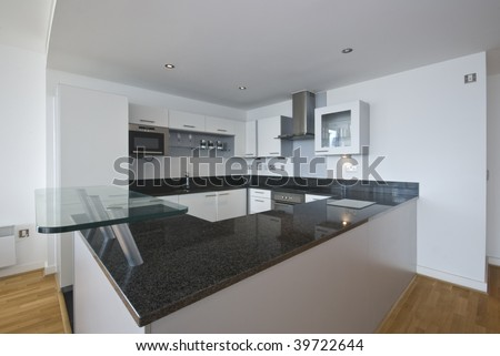 fully fitted modern kitchen in white with appliances - stock photo